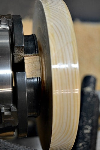 parting off the larch trivet from the lathe
